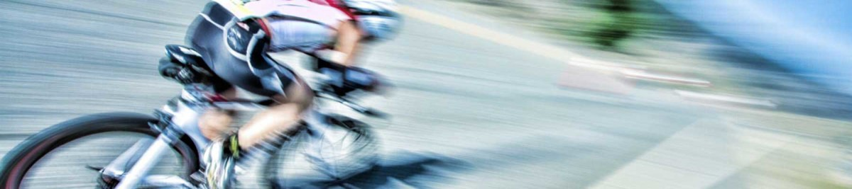 Biker rides by the camera with significant blur effect