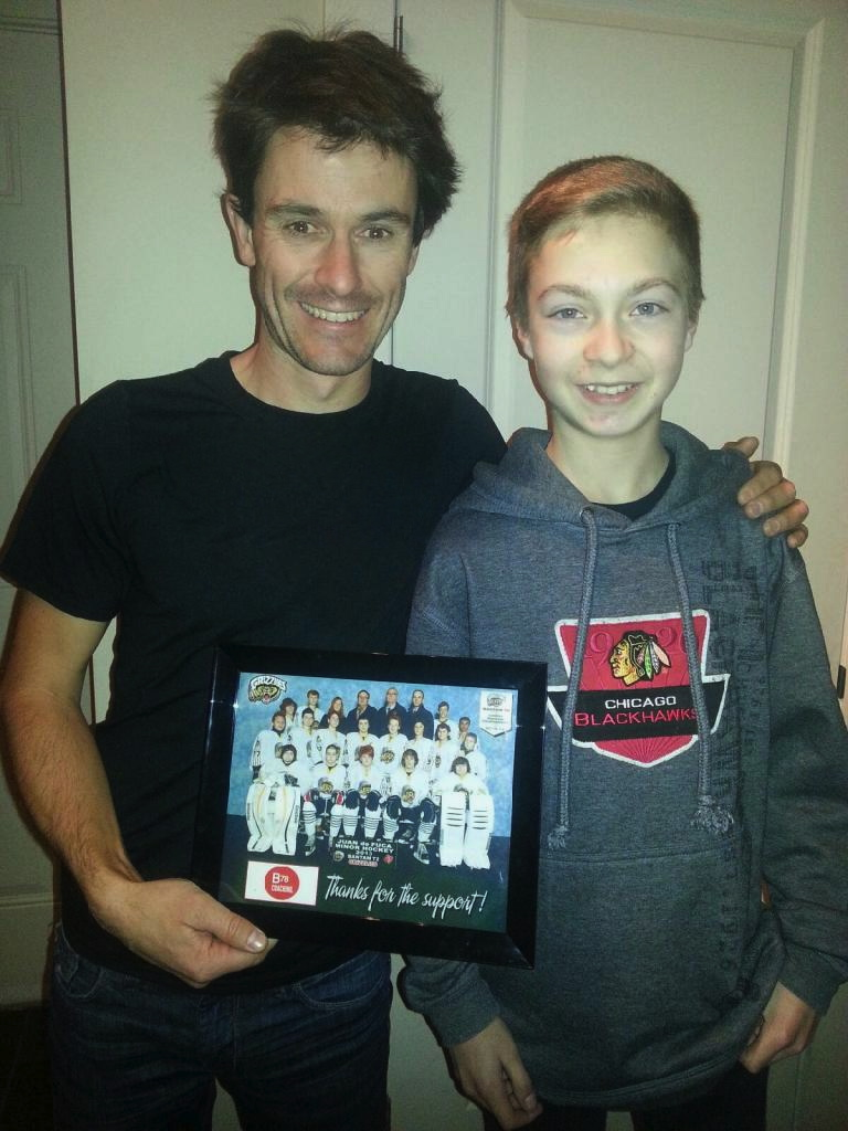 Coach Jasper Blake with young Landen Shaw holding a picture of his Bantam hockey team