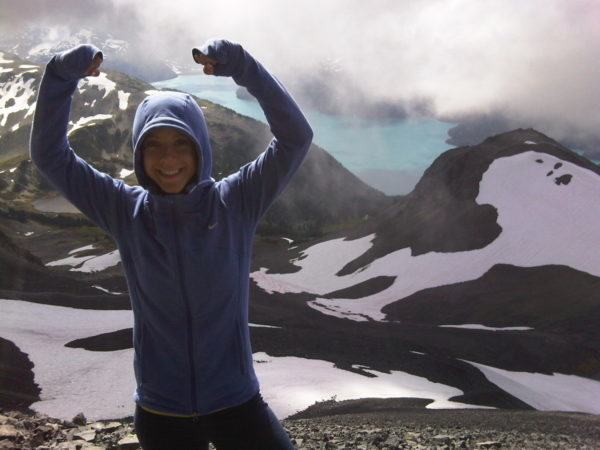 Leah Plumridge raising her arms with joy on a mountain
