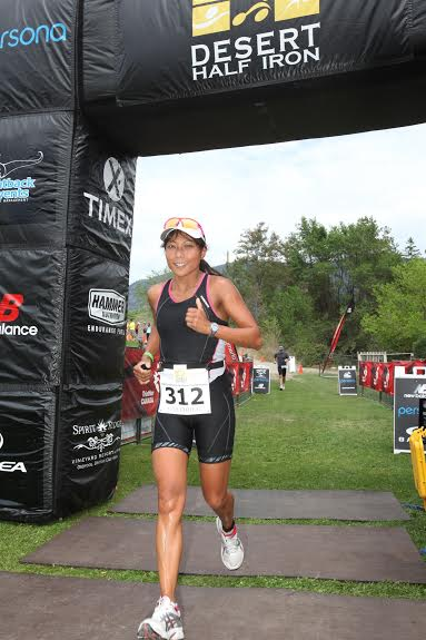 Gail Chung crosses the finish line of a triathlon, and is still smiling