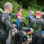 Athletes in wetsuits getting ready for a swim
