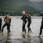 Swimmers at Ironman Canada Training camp walking slowly into the water