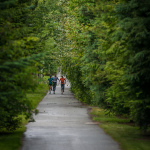 Athletes running down a green enclosed path while training for Ironman Canada