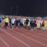 Group running on a track at night
