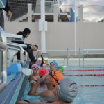 Swimmers wait anxiously at the side of the pool before starting a swim set