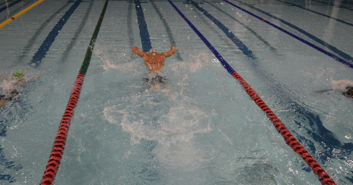 A swimmer swimming in a pool with lane ropes