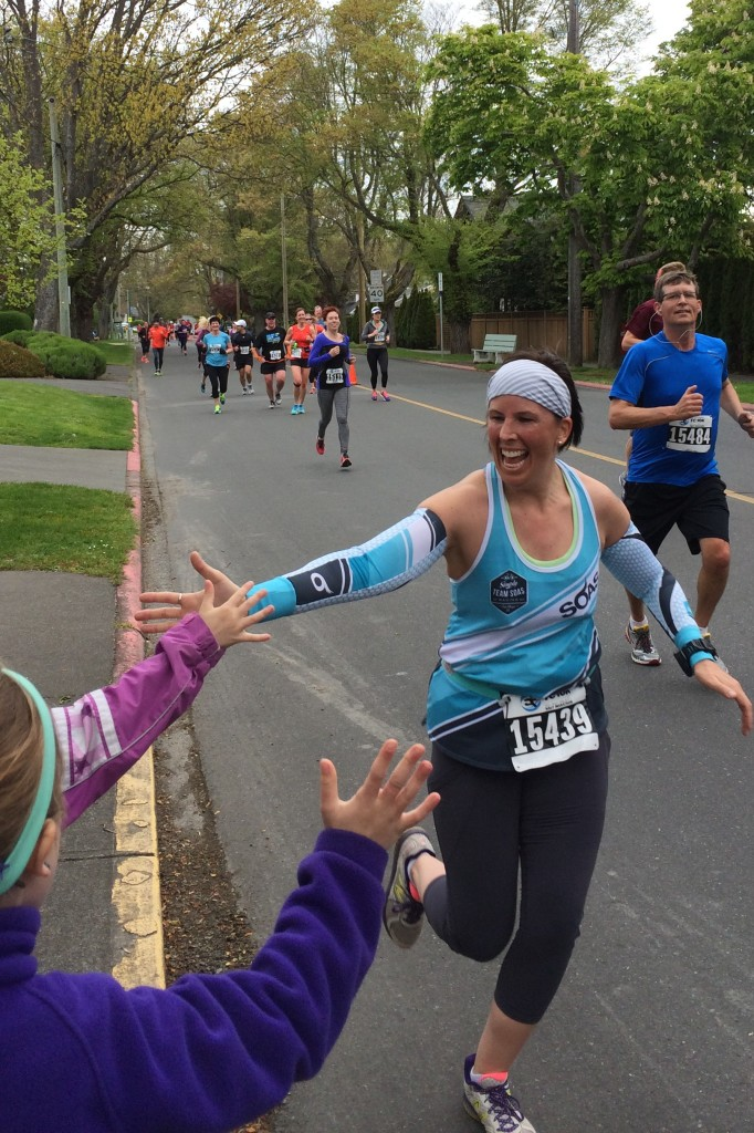 A runner high fives some people who are on the side of the road cheering
