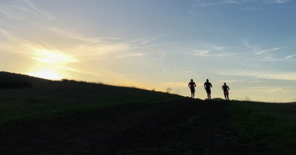 Three runners crest a hill into the sunset.