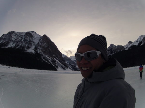 A man whose chest is facing the left is turning his head to smile at the camera. He has a tuque, sunglasses, and a winter jacket on. There are snow covered mountains and snowy ground behind him. The sky is bright and grey.