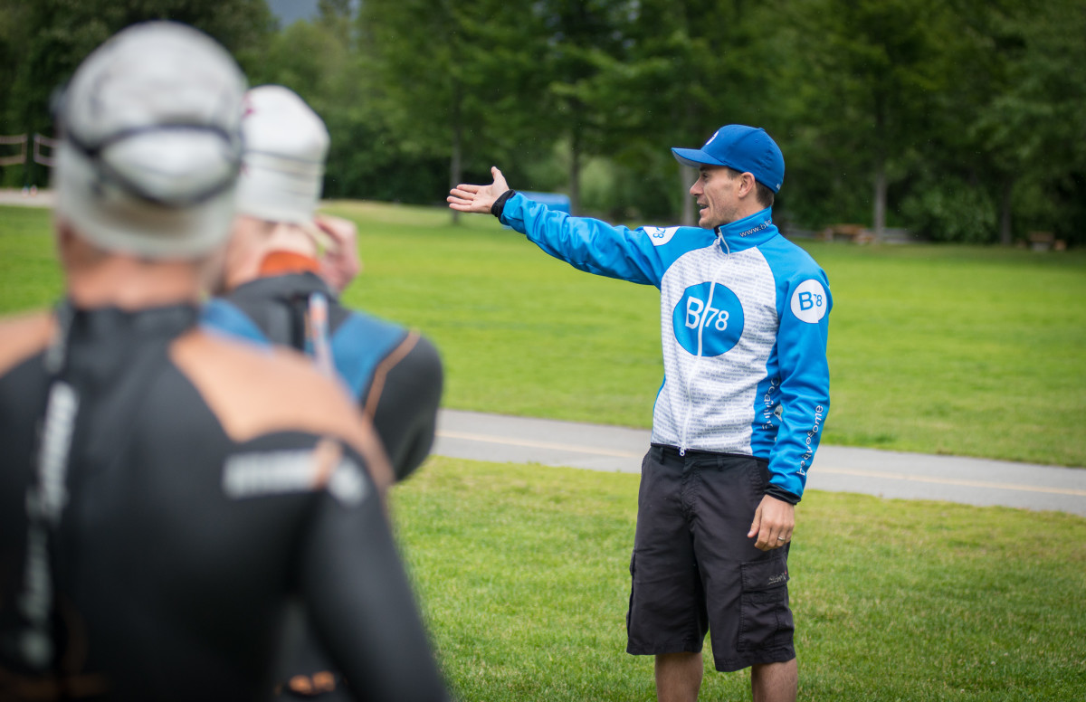 Coach Jasper Blake directing swimmers at Ironman Canada Training Camp. He is standing on grass with trees behind him in a blue and white B78 sweatshirt and blue cap. There are two figures out of focus in the foreground.