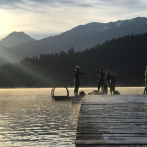 B78 athletes prepare for training, on a dock on a stunning morning in the mountains.