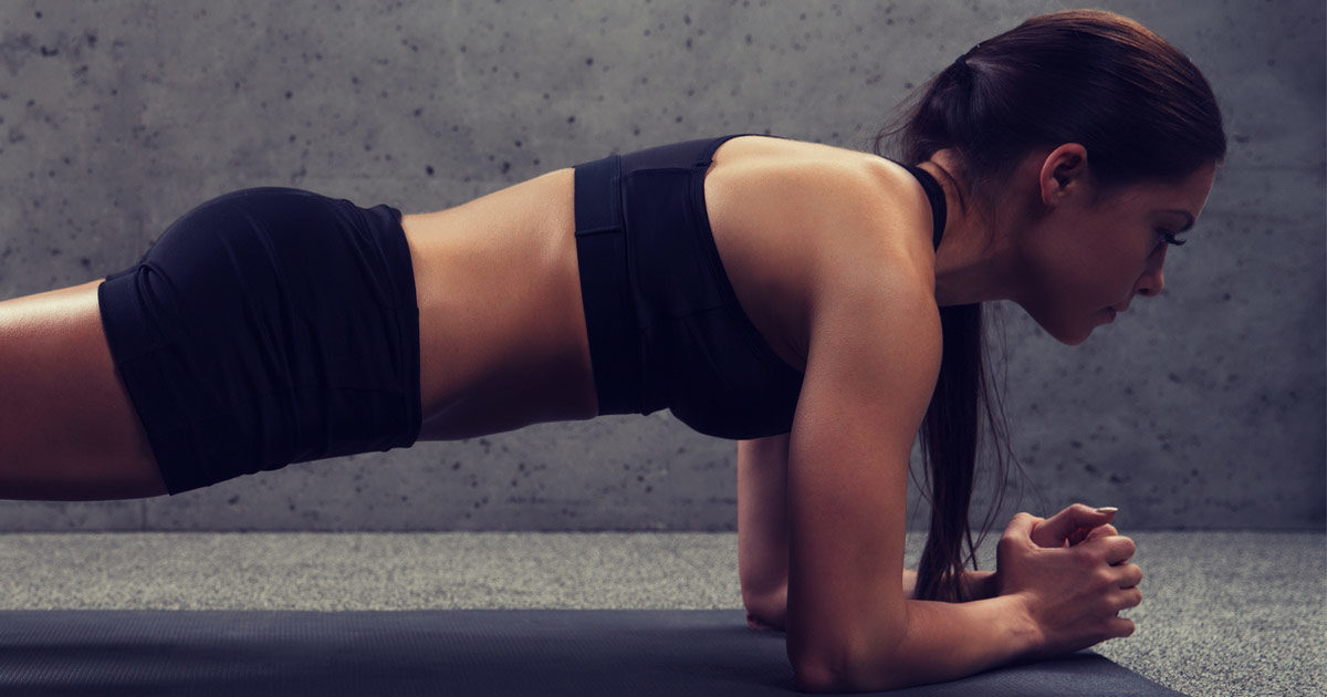 Close up of a woman doing plank at her gym on the mat.