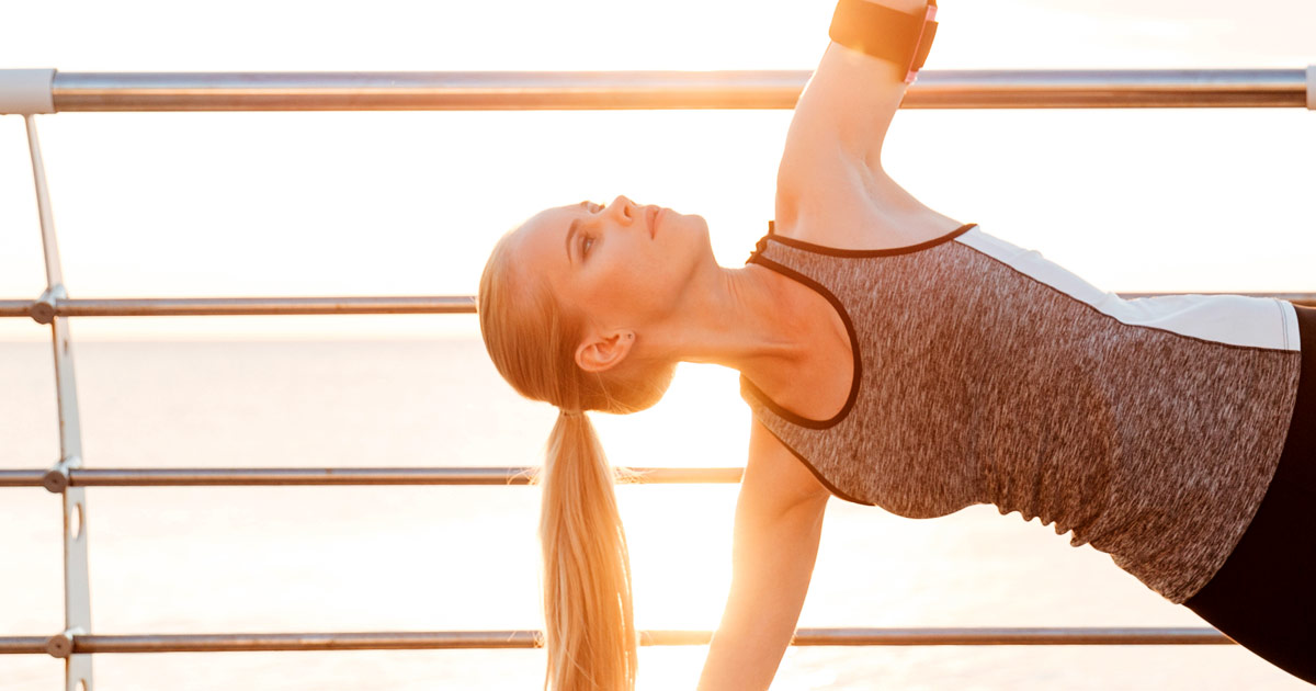 A woman out on the boardwalk, does a plank or side plank in the sunlight.
