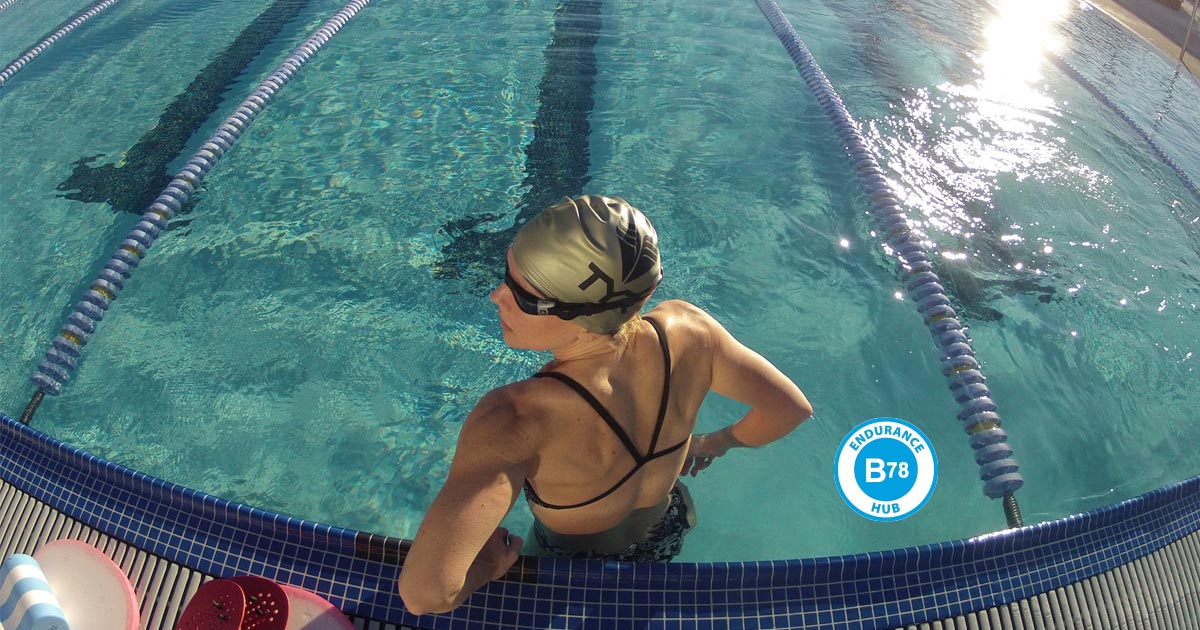 A swimmer rests between sets, next to a B78 Endurance Hub logo.